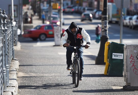 A man on his bicycle braves the cold as he makes his way along Main Street in Paterson on 02/19/19.