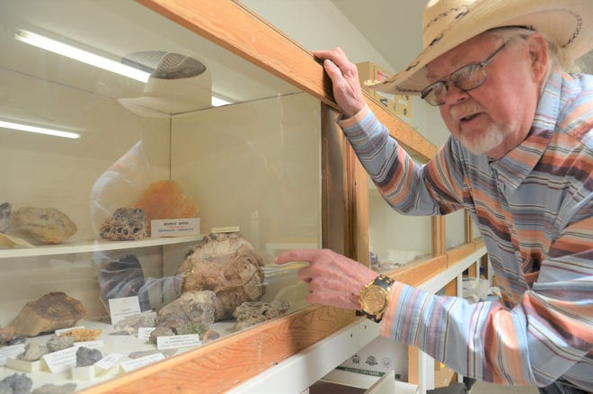 Dr. John Edwards, president of the Deming Gem and Mineral Society, points out petrified wood displayed in a showcase at the Gem and Mineral Society Clubhouse located at 4200 Raymond Reed Blvd.