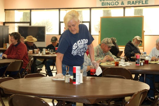Volunteer Angelica Portillo helps keep the dining room at the Deming Senior Citizens' Center tidy.