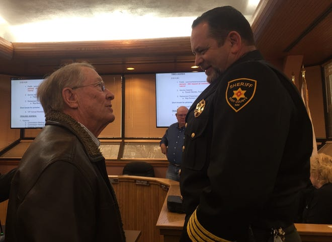Jim Carr (left) and Eddy County Sheriff Mark Cage visit after the Eddy County Board of Commissioners voted Feb. 19 to support citizens' firearms rights.