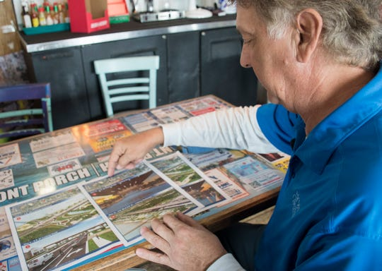 Bobby Benaquis, owner of TC's Front Porch, looks over renderings of the proposed flyover along Navarre Parkway/I-98 in Navarre Beach on Tuesday, February 19, 2019.