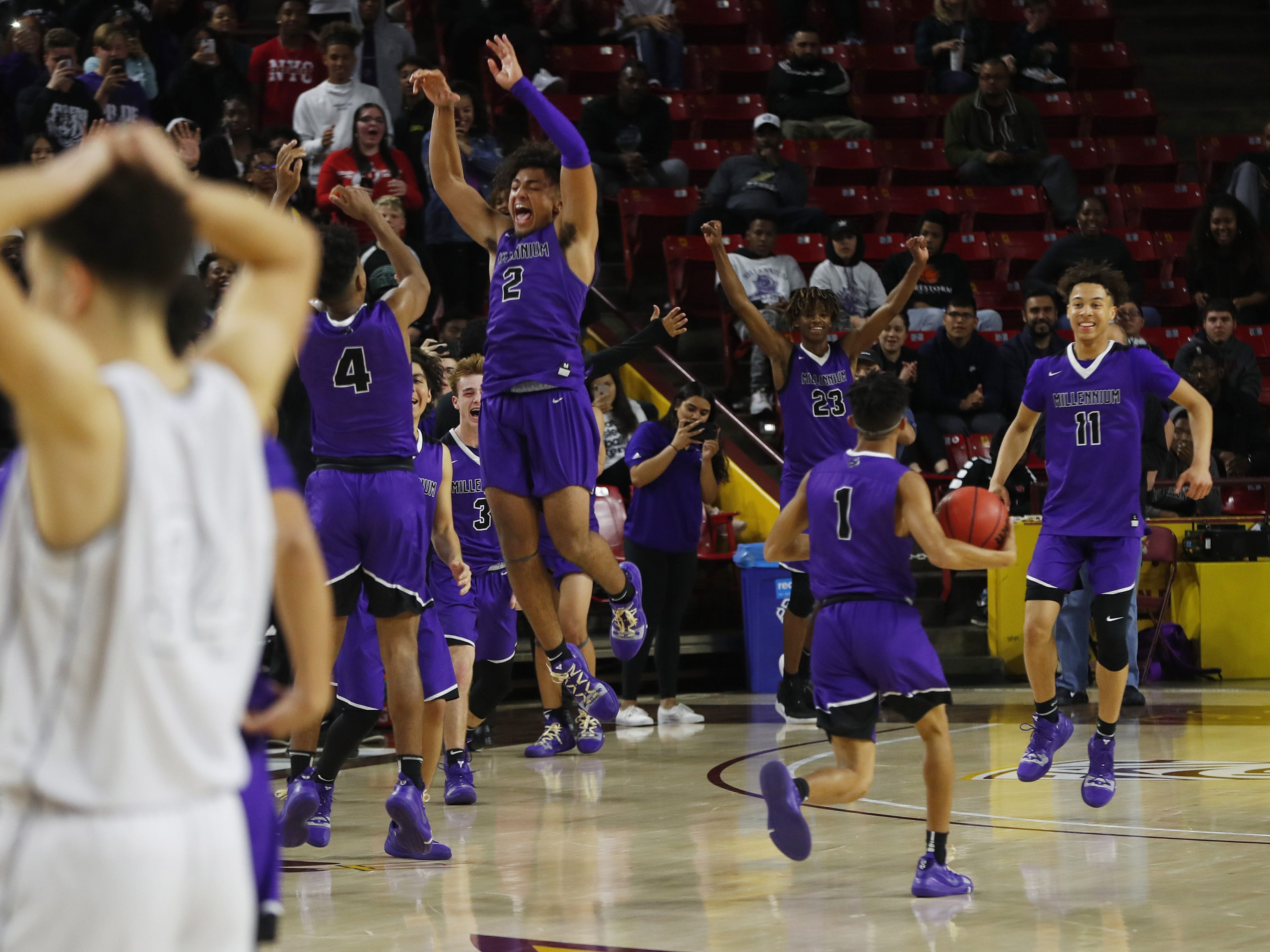 Millennium's Jalan Early (2) celebrates with his teammates as Apollo's Demetrius Edwards (34) puts his hands on his head following a Millennium win over favored Apollo during the 5A boys basketball state semifinal game at Wells Fargo Arena in Tempe, Ariz. on February 18, 2019.