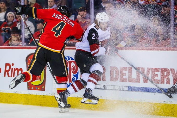 Feb 18, 2019: Arizona Coyotes right wing Mario Kempe (29) and Calgary Flames defenseman Rasmus Andersson (4) battle for the puck during the second period at Scotiabank Saddledome.