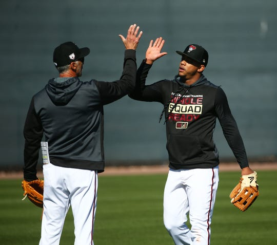Arizona Diamondbacks coach Dave McKay high-fives Ketel Marte during spring training workouts on Feb. 19 at Salt River Fields in Scottsdale, Ariz.
