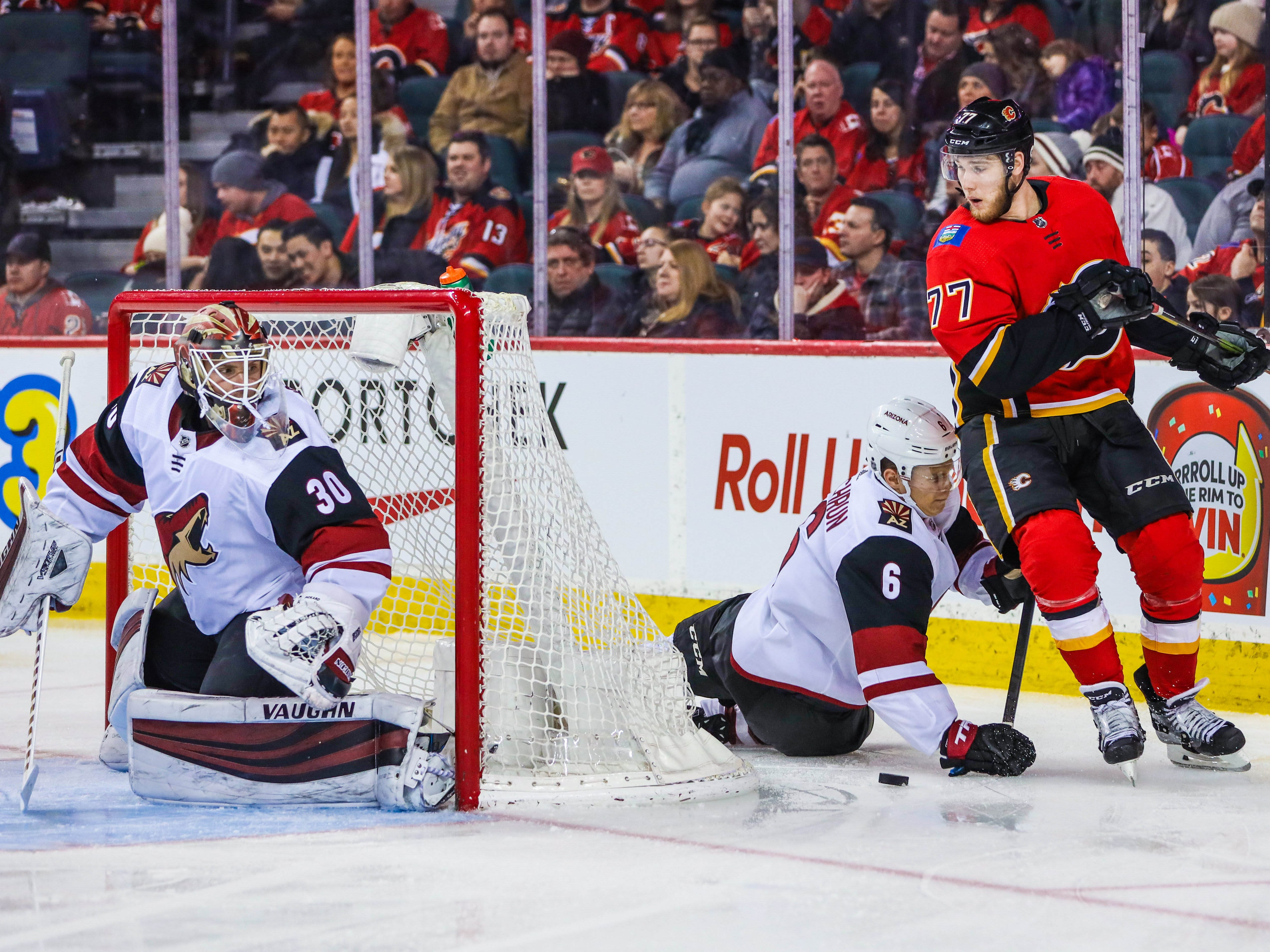 Feb 18, 2019; Calgary, Alberta, CAN; Arizona Coyotes defenseman Jakob Chychrun (6) and Calgary Flames center Mark Jankowski (77) battle for the puck as Arizona Coyotes goaltender Calvin Pickard (30) guards his net during the third period at Scotiabank Saddledome. Calgary Flames won 5-2. Mandatory Credit: Sergei Belski-USA TODAY Sports