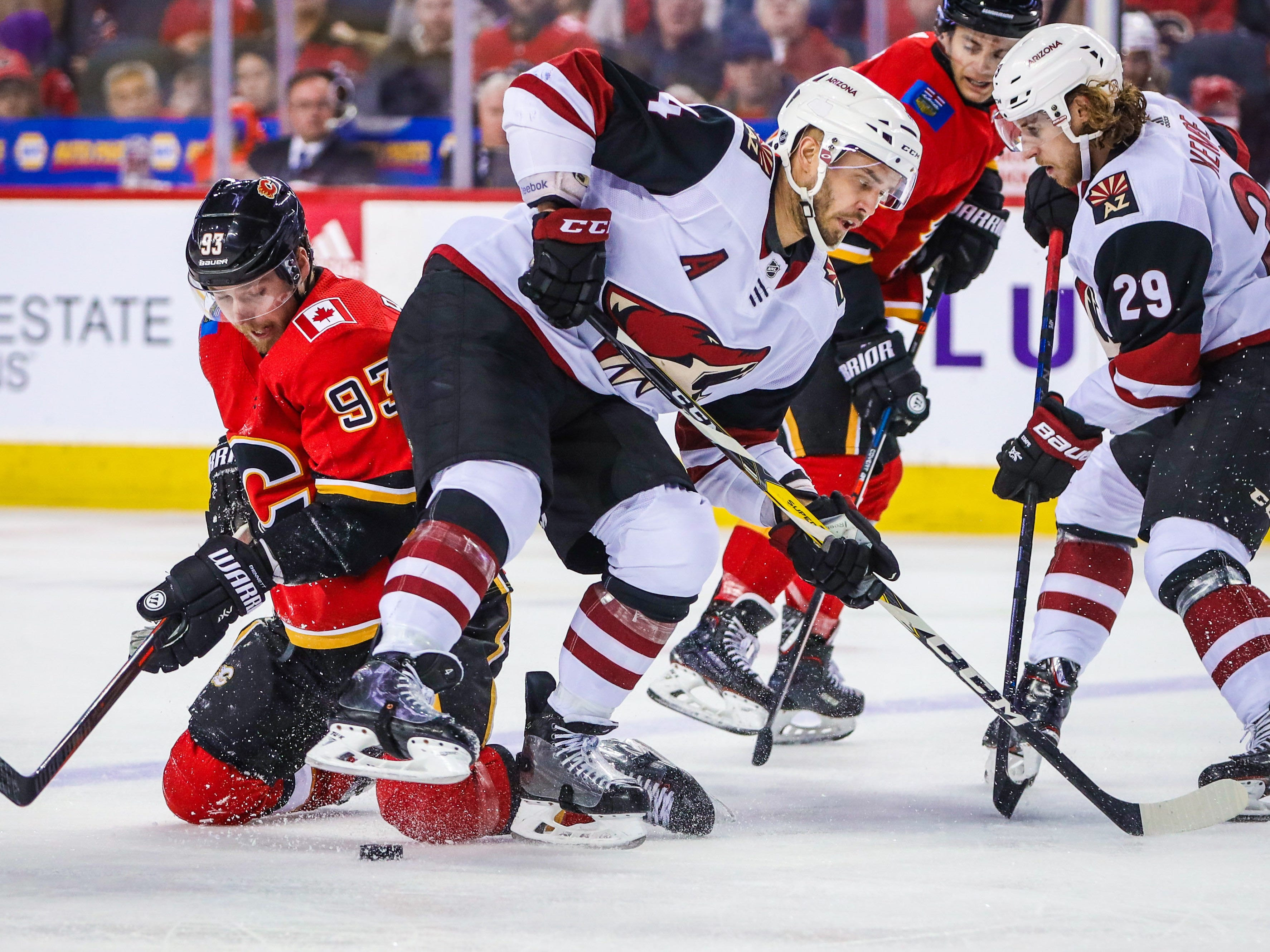 Feb 18, 2019; Calgary, Alberta, CAN; Calgary Flames center Sam Bennett (93) and Arizona Coyotes defenseman Niklas Hjalmarsson (4) battle for the puck during the third period at Scotiabank Saddledome. Calgary Flames won 5-2. Mandatory Credit: Sergei Belski-USA TODAY Sports