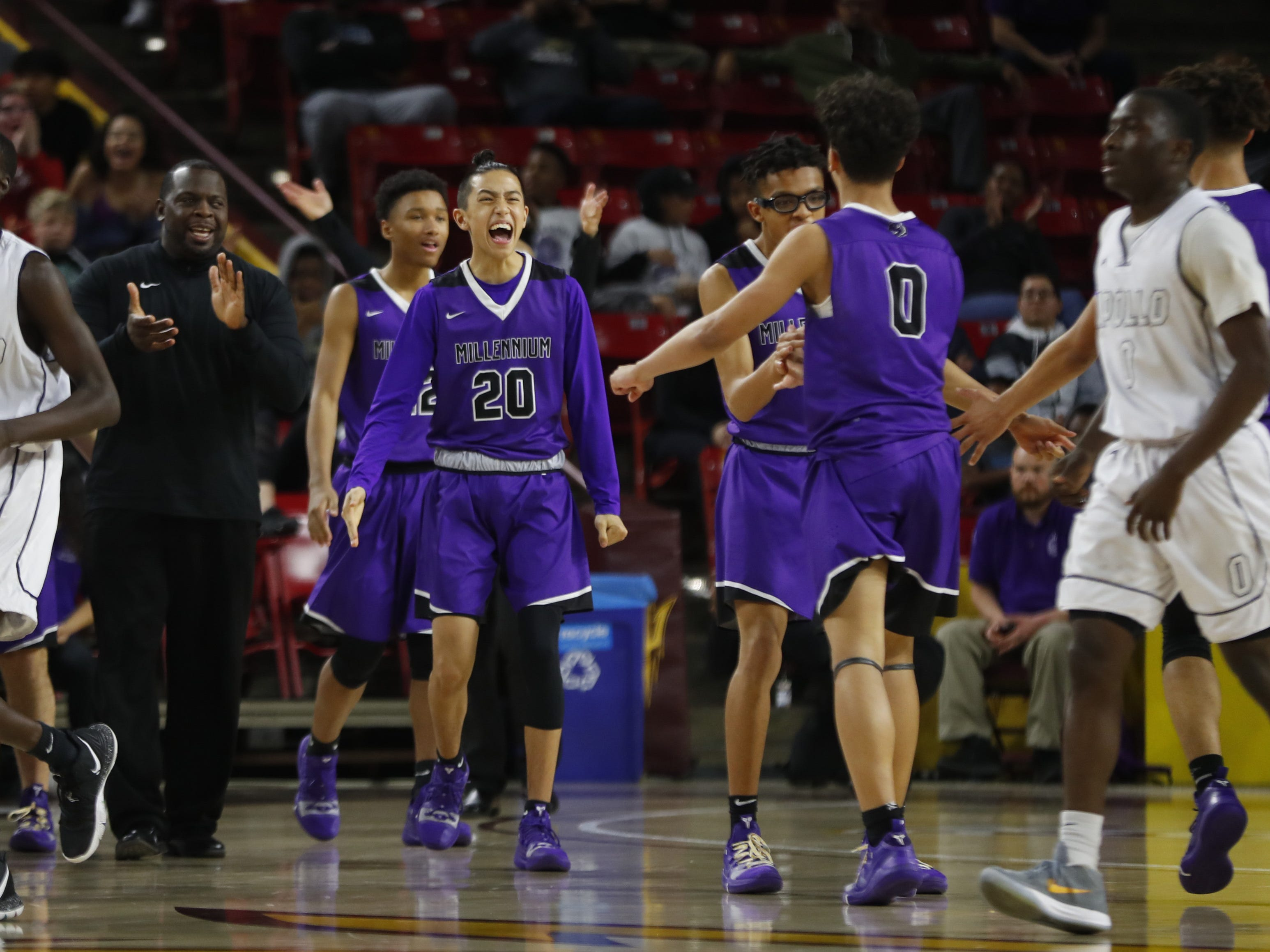 Millennium's Donovan Castro (20) comes onto the court to celebrate with Justus Jackson (0) after the team forces an Apollo timeout during the 5A boys basketball state semifinal game at Wells Fargo Arena in Tempe, Ariz. on February 18, 2019.
