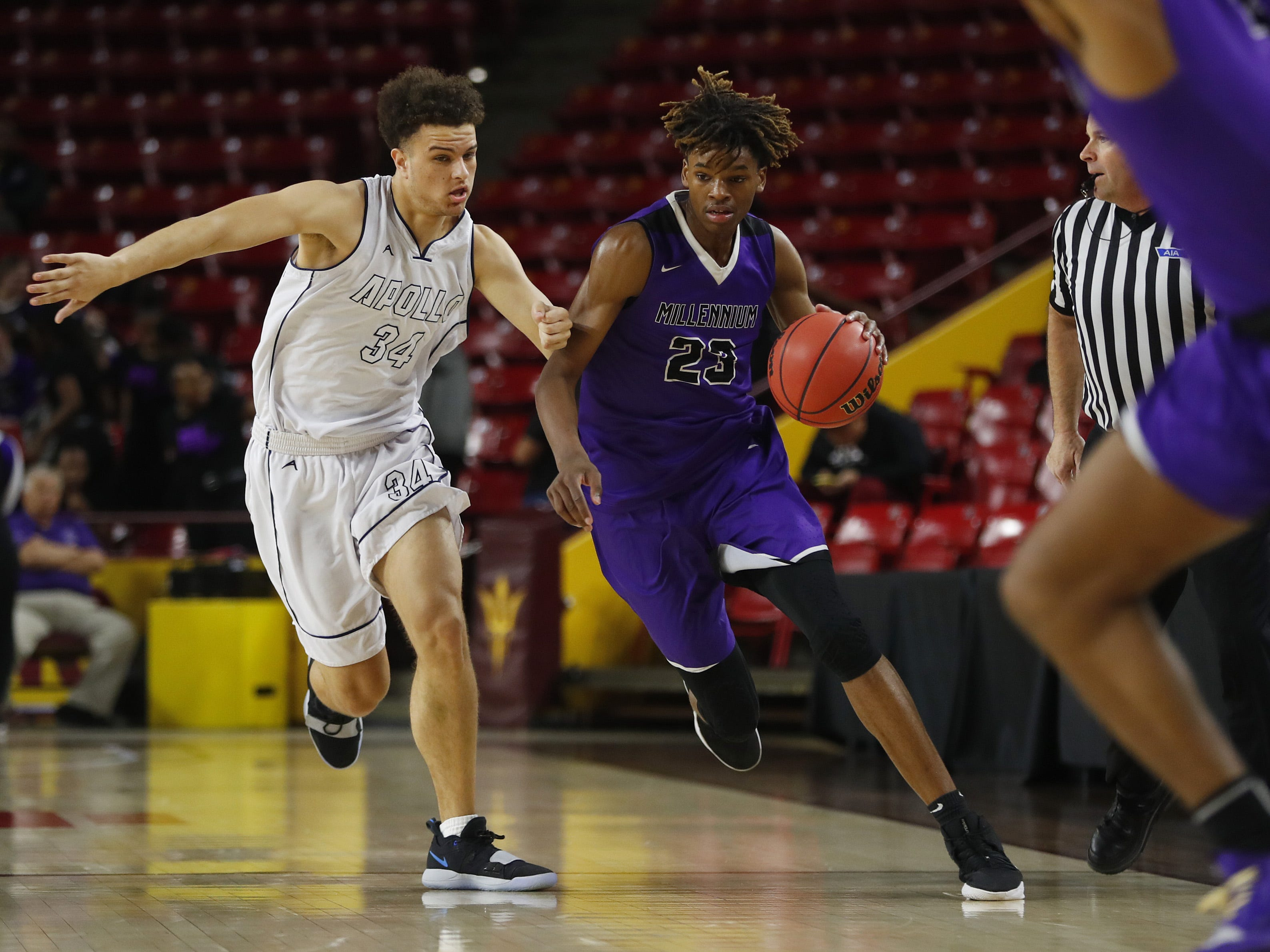 Millennium's DaRon Holmes (23) dribbles against Apollo's Demetrius Edwards (34) during the 5A boys basketball state semifinal game at Wells Fargo Arena in Tempe, Ariz. on February 18, 2019.