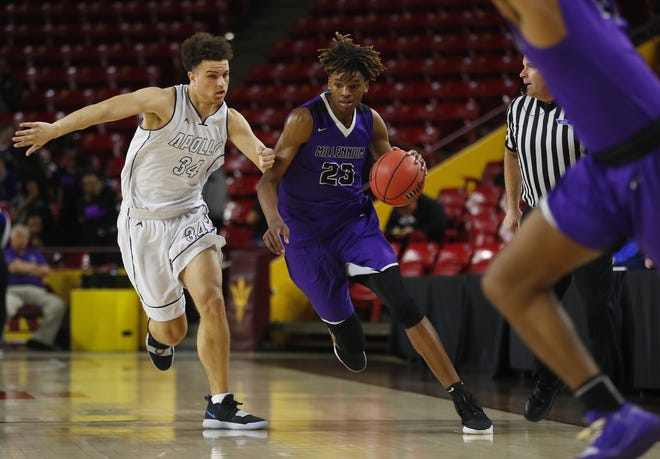 Millenium's DaRon Holmes dribbles past Apollo's Demetrius Edwards during a 5A boys basketball state semifinal game on Feb. 18.