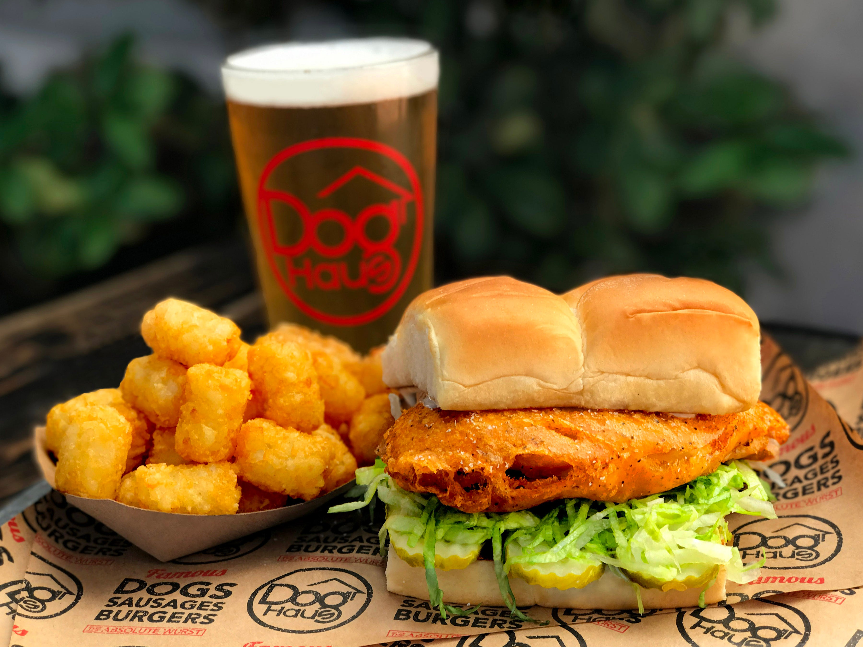Among Dog Haus' menu items are beer, tater tots and burgers, like the Bad Mutha Clucka, a beer battered chicken breast topped with lettuce, pickles and miso ranch.