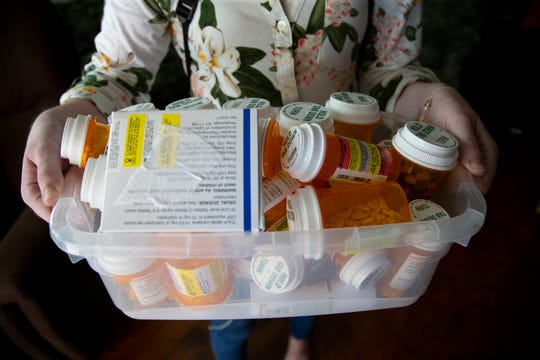 Caitlin Secrist's daily medication bottles  overflow a large, plastic box.