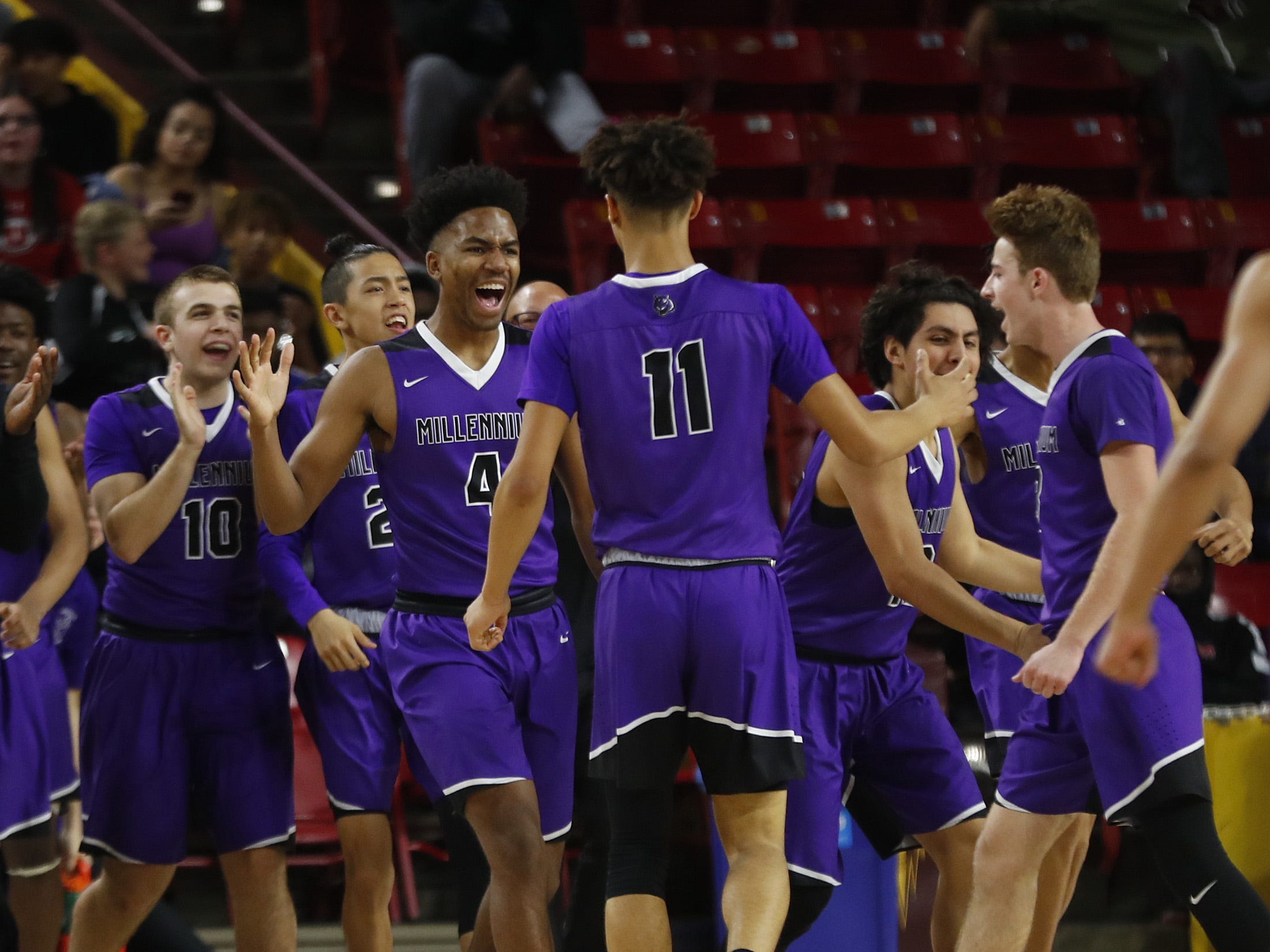 Millennium's Caleb Wright (4) celebrates with Coleman Fields (11) after a basket and a Apollo timeout during the 5A boys basketball state semifinal game at Wells Fargo Arena in Tempe, Ariz. on February 18, 2019.