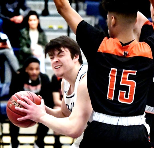 West York's Gabe Mummert is defended under the basket by Northeastern's Maurice Capo during a District 3 Class 5-A boys' basketball first-round game at West York Monday, Feb. 18, 2019. Bill Kalina photo