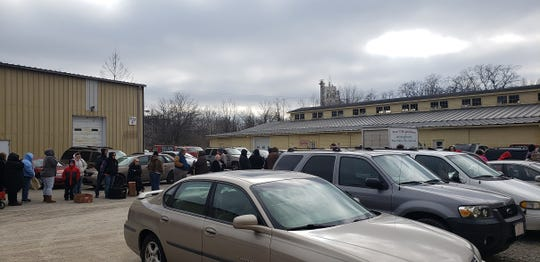 Families line up Saturday to receive free food at Gateway Hunger Relief Center in Richmond.