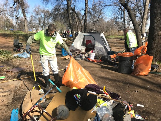 Volunteers with Shasta Support Service help police Tuesday clean up a homeless camp in Parkview Riverfront Park in Redding.