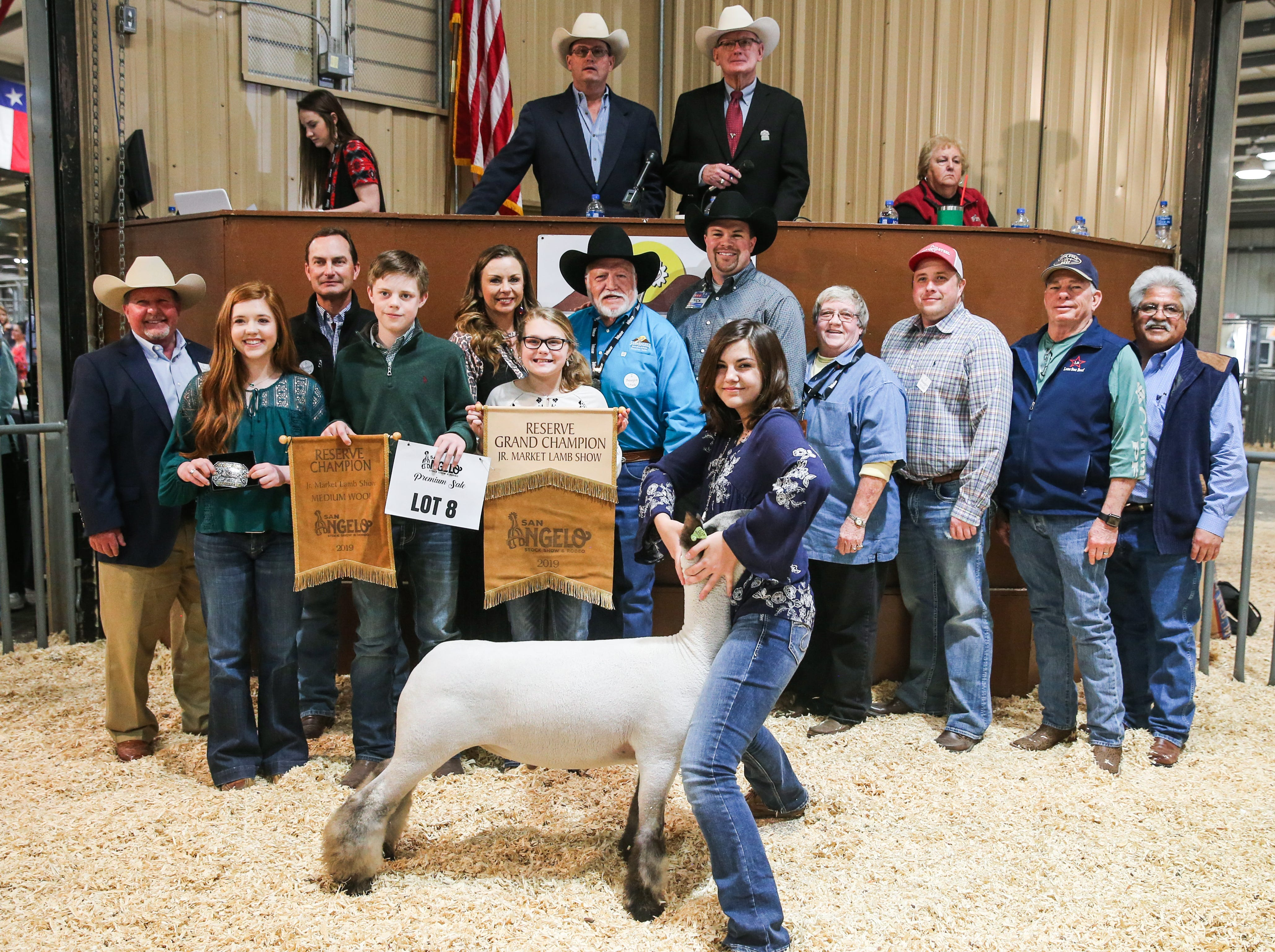 Reserve Grand Champion Lamb exhibited by Kaitlin Chabot of Falls County 4-H, sold for $14,000.From left to right: Todd Price, Jim Bass Ford; Carlye Winfrey (holding buckle), John Mayer, Mayer Ranch; Hudson Franklin (holding banner); Bridget Carr, Carr Clinic; McKinley Clem (holiding banner); Clay Cross, Cross Country Construction; Nick George, H-E-B; Kaitlin Chabot (exhibitor); Patsy McIntire, Bug Express; Bubba Davis, West Texas Steel; Chuck Jones, Lone Star Beef; Raymond Meza, Twin Mountain Fence Company. Not pictured: Neff Livestock/Texas Water & Soil, Weatherby Ranch, Saddletramp Land & Cattle.