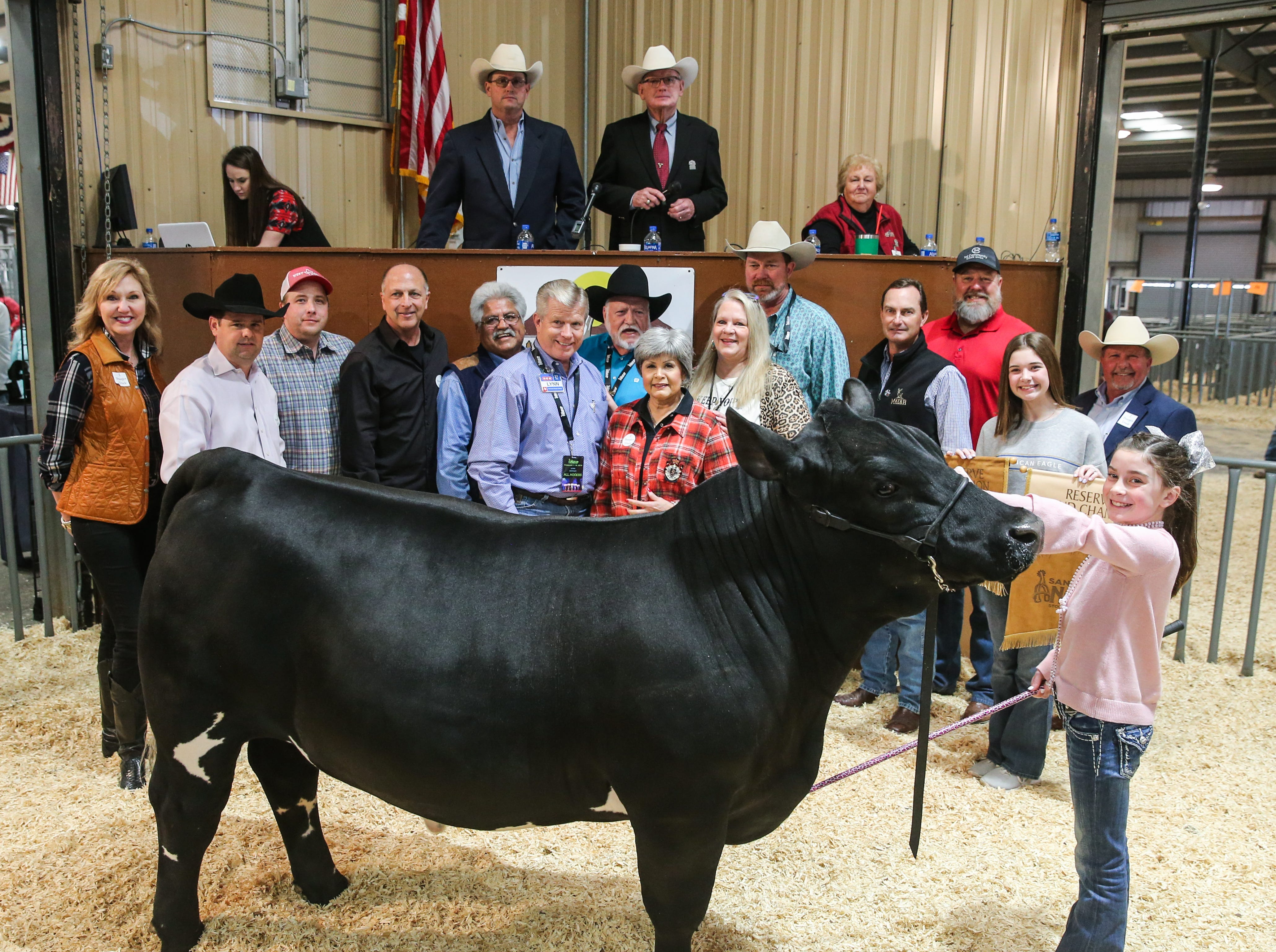 Reserve Grand Champion Steer exhibited by London Bird of Lubbock County 4-H, sold for $25,000.From left to right: Sherry Goode, Firehouse Auto Works; Tommy Neal, Edward Jones; Bubba Davis, West Texas Steel; Phil Gandy, Gandy Ink; Raymond Meza, Twin Mountain Fence; Lynn Shipley, H-E-B; Clay Cross, Cross Country Construction; Toni Sudduth, Trans Texas Southwest Credit Union; Debbie Cross, Cross Cuts Salon; Derek Morrison, Southern Glazer's Wine and Spirits; John Mayer, Mayer Ranch; Bill Nikolauk, 1st Community Federal Credit Union; Berkley Bird (holding banner); Todd Price, Jim Bass Ford; London Bird, exhibitor. Not pictured: Weatherby Ranch.