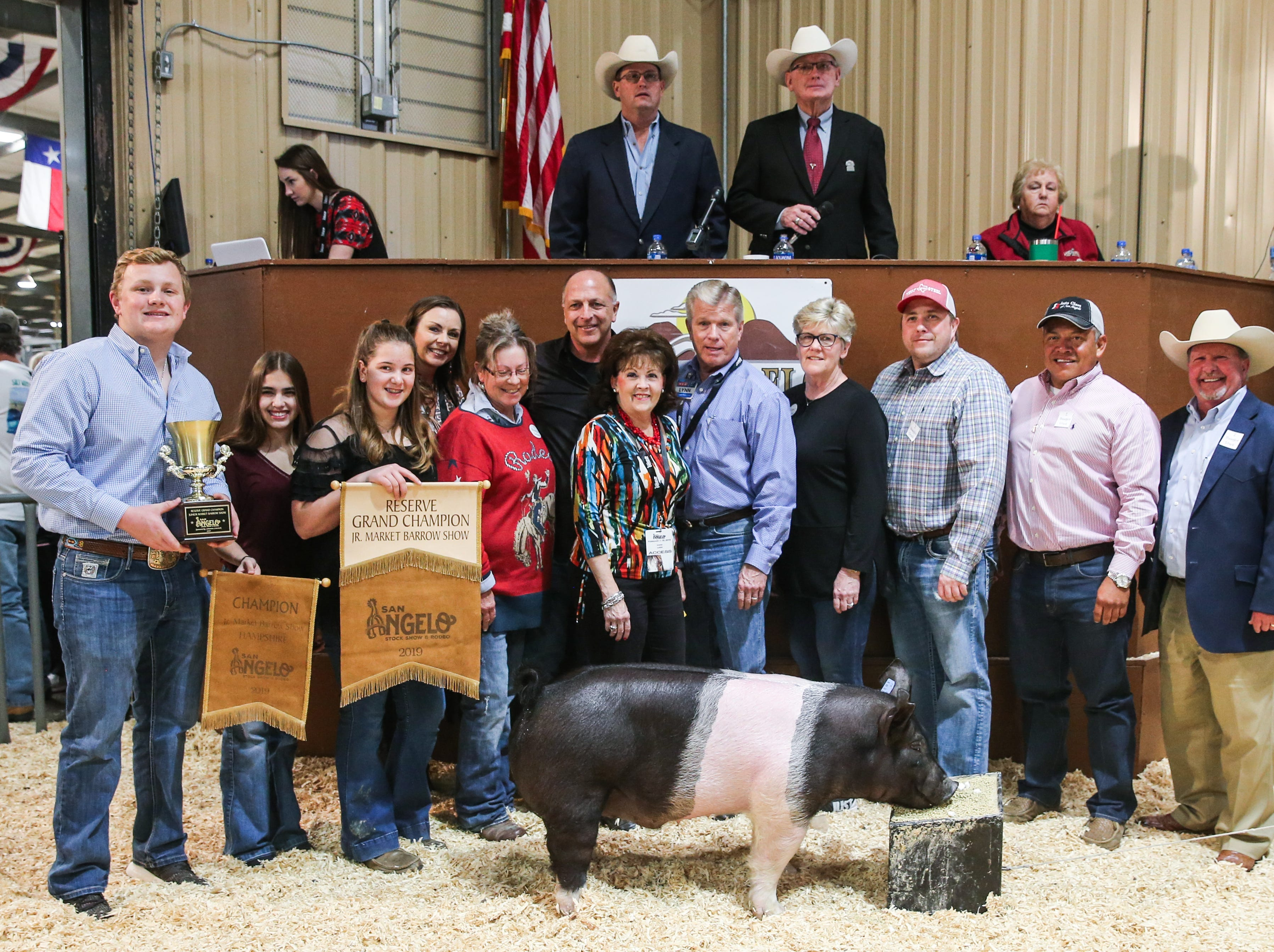Reserve Grand Champion Barrow exhibited by Dakota Martin of Mason County 4-H, sold for $12,000.From left to right: Slone Stultz (holding trophy); Kary Humphrey (holding banner); Dakota Martin (exhibitor); Bridget Carr, Carr Clinic; Dawn Foster, No Step Ranch; Phil Gandy, Gandy Ink; Vicki Loso, 1st Community Credit Union; Lynn Shipley, H-E-B; Pattie Self, Automatic Fire Protection; Bubba Davis, West Texas Steel; Johnny Castillo, GA Auto Glass; Todd Price, Jim Bass Ford. Not pictured: Neff Livestock/Texas Water & Soil, W&W AFCO Steel- Hirschfeld Division, Sendero Drilling.