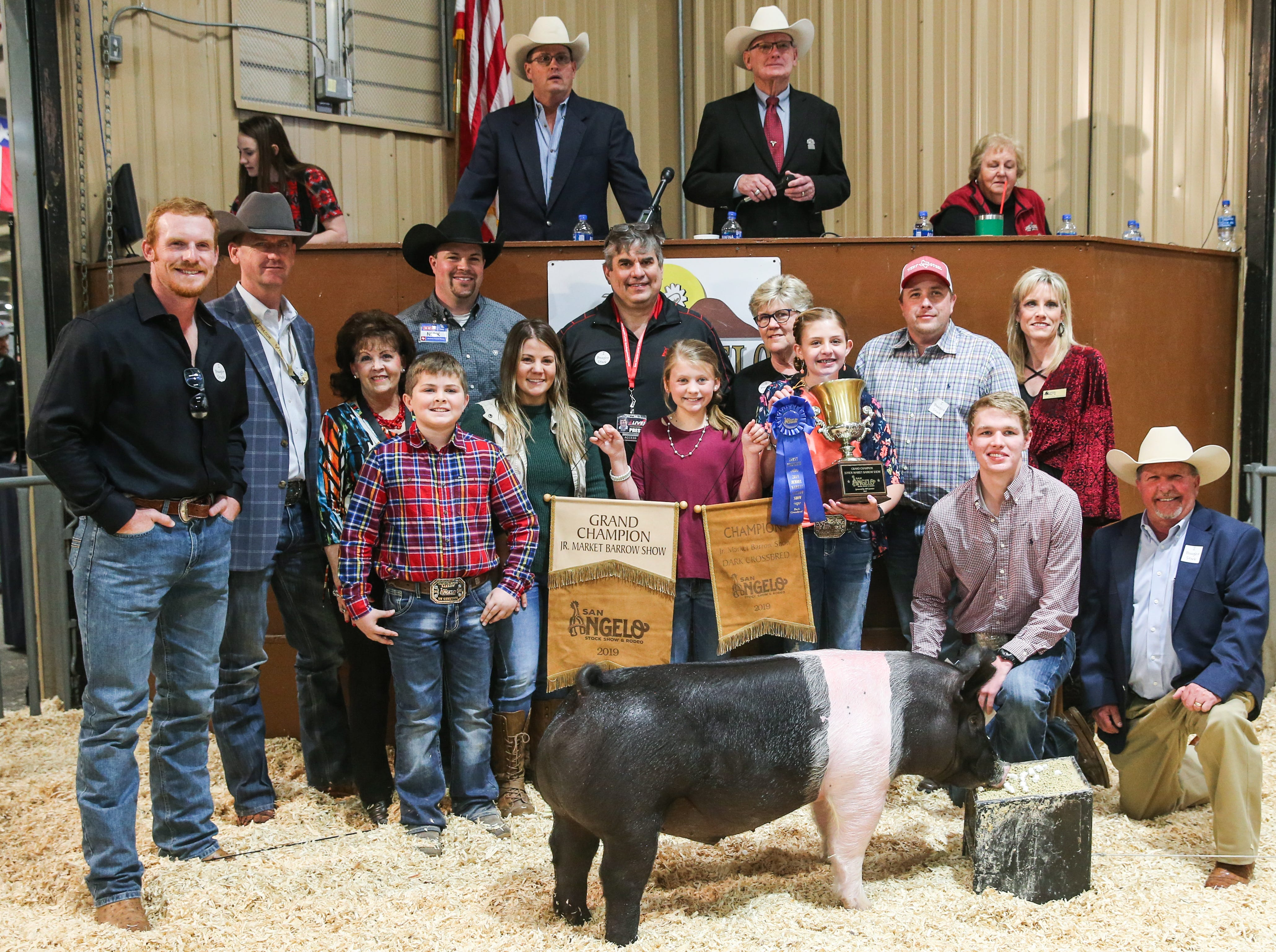 Grand Champion Barrow exhibited by Kaden Mason of Montgomery County 4-H, sold for $13,000.From left to right: Rush Seaver, 1CFCU Insurance Services; Sean Carter, Gandy Ink; Vicki Loso, 1st Community Federal Credit Union; Kaden Mason (exhibitor); Nick George, H-E-B; Sara Konop, Taco Bueno; Joe Hyde, San Angelo Live; Kendall Shackelford (banner holder); Pattie Self, Automatic Fire Protection; McKinley Tucker (trophy holder); Bubba Davis, West Texas Steel; Nolan McGarraugh (holding lot number); Karee Wiggins, Capital Farm Credit; Todd Price, Jim Bass Ford. Not pictured: Intrepid Electric, Weatherby Ranch, and Housley Communications.