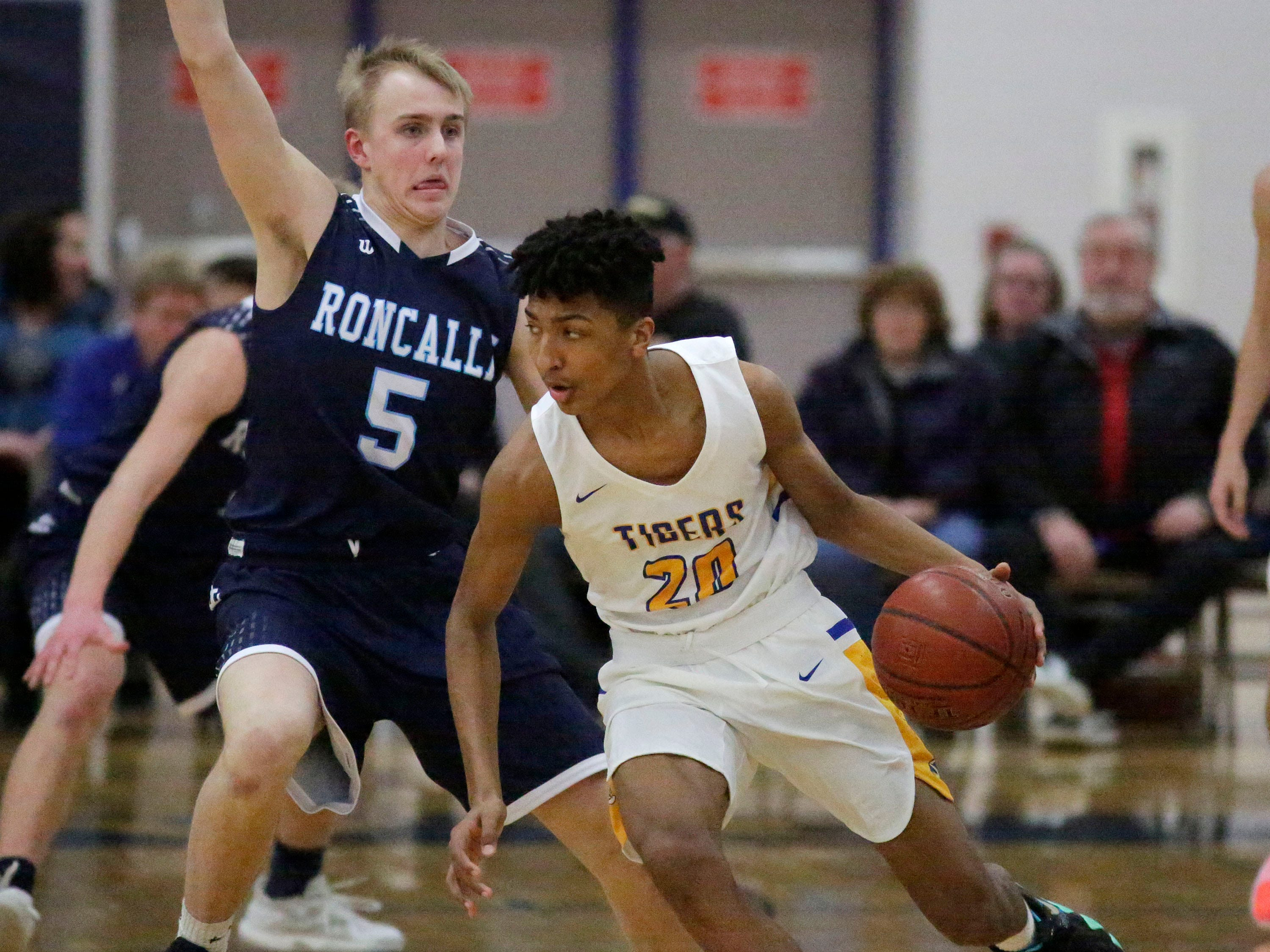 Howards Grove's Kaden Summerville (20) drives the ball around Roncalli's Lujke Pautz (5), Monday, February 18, 2019, at Howards Grove, Wis.