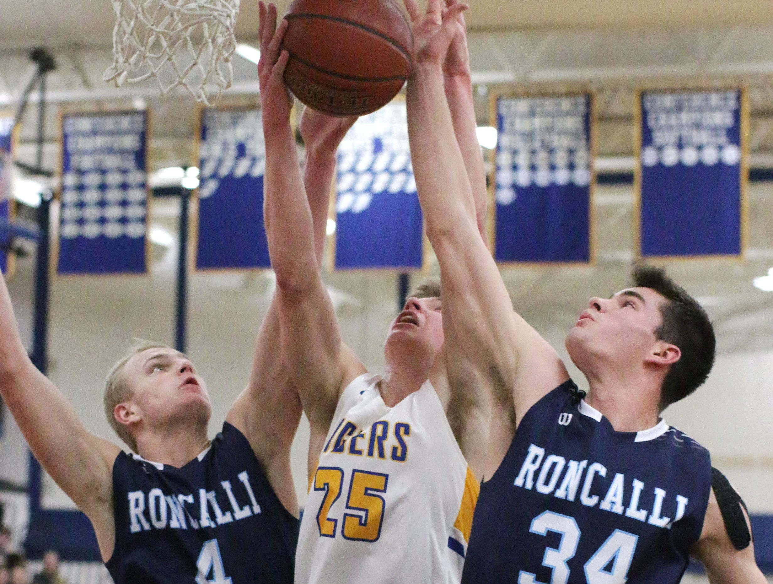 Howards Grove's Jack Baldwin (25) rebounds the ball by Roncalli's Bryce Pautz (4) and Ian Behringer (34), Monday, February 18, 2019, at Howards Grove, Wis.