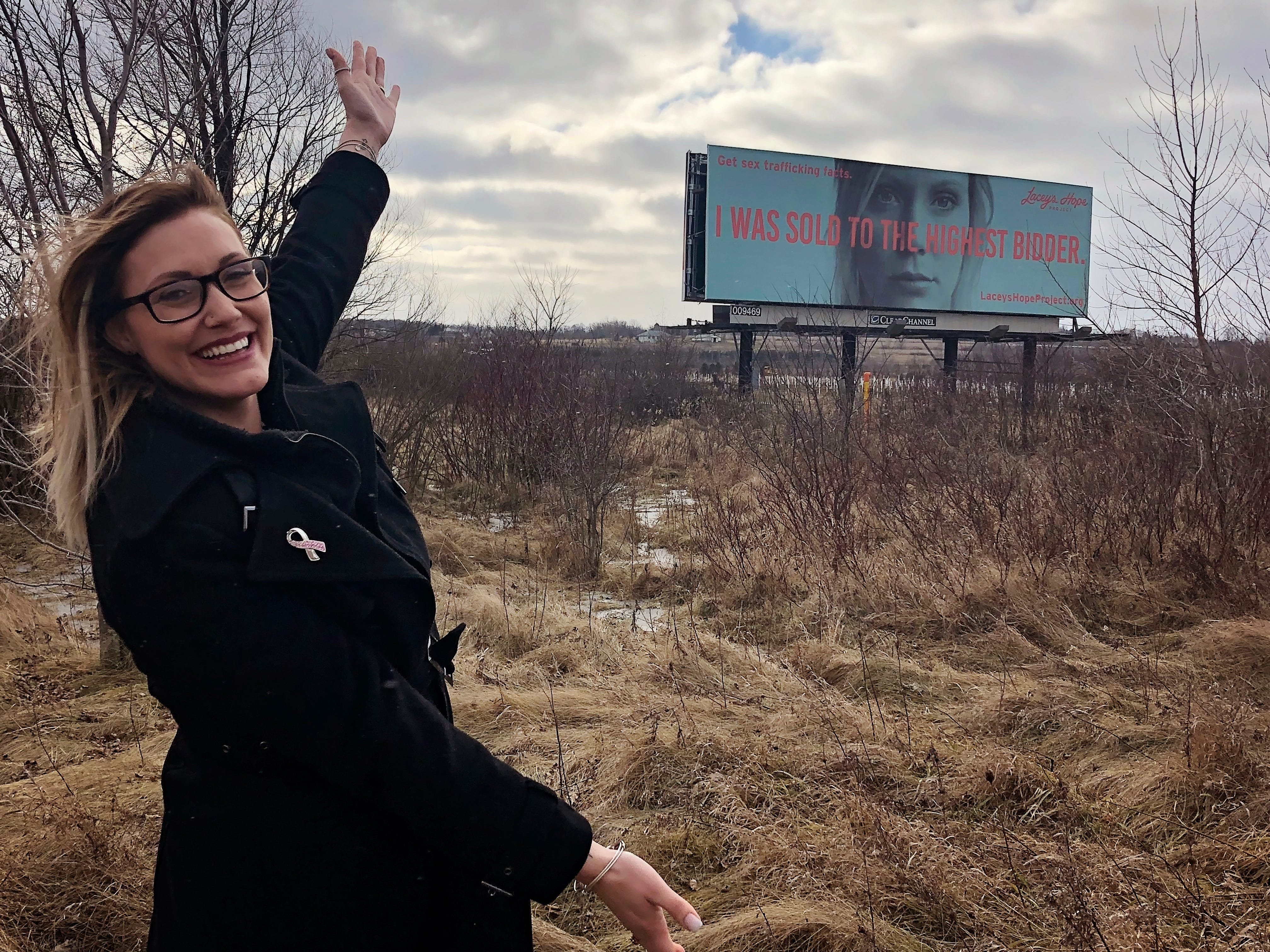"""Emmy Meyers survived sex trafficking. Here she stands by a billboard featuring a poster from the campaign """"Your Suburbs Aren't Safe."""" The campaign is part of the mission of Lacey's Hope Project, a nonprofit Meyers founded to raise awareness about sex trafficking."""