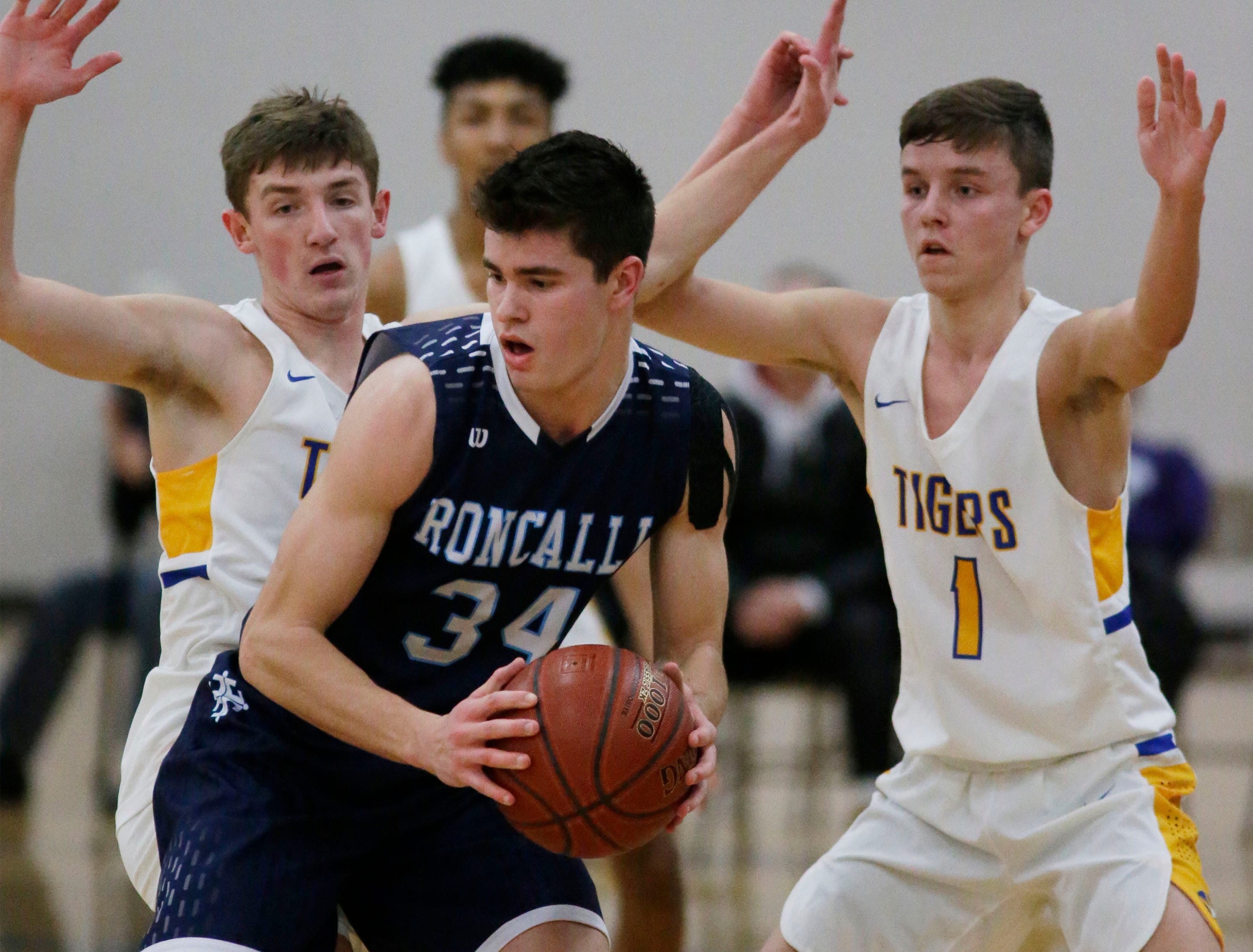 Roncalli's Ian Behringer (34) works the ball around Howards Grove, Monday, February 18, 2019, at Howards Grove, Wis.