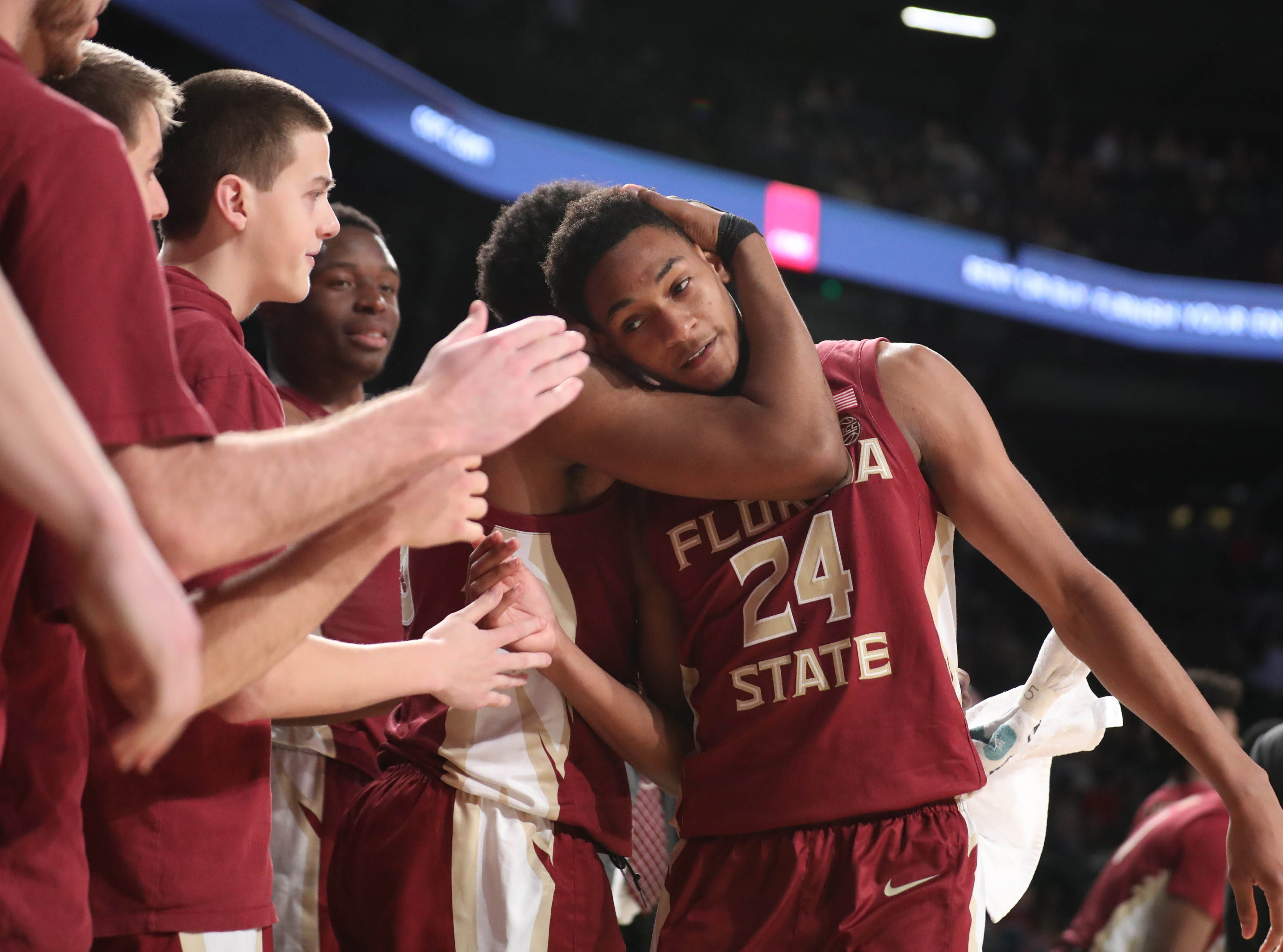 Feb 16, 2019; Atlanta, GA, USA; Florida State Seminoles guard Devin Vassell (24) gets a hug from guard PJ Savoy (5) after Vassell returned to the bench in the second half against the Georgia Tech Yellow Jackets at McCamish Pavilion. Mandatory Credit: Jason Getz-USA TODAY Sports