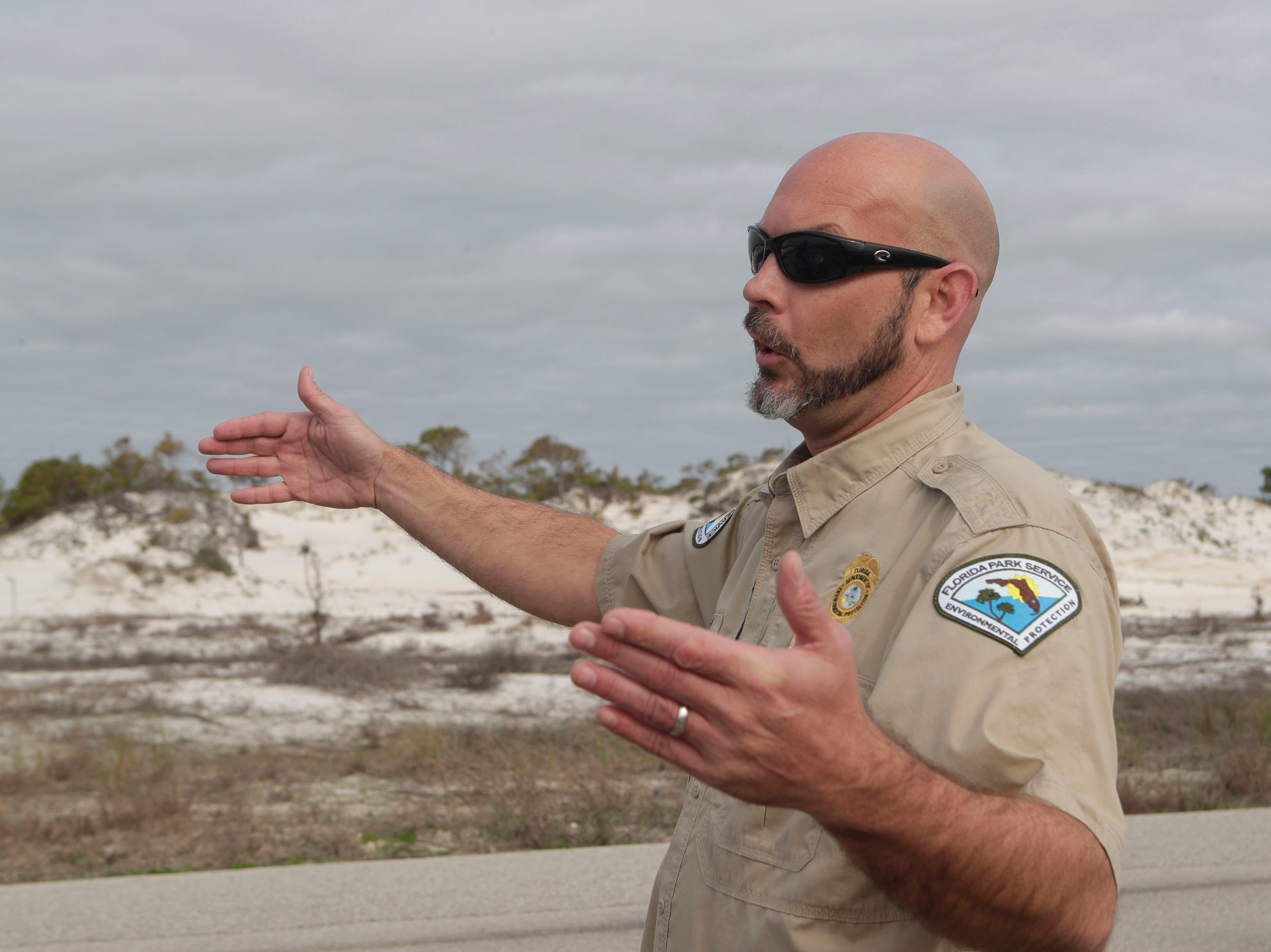 Josh Hodson, park ranger at St. George Island State Park, talks about how the dunes closer to shore were washed away during Hurricane Michael in Oct. 2018. The dunes across the street from the beachfront are untouched, Tuesday Feb. 19, 2018.
