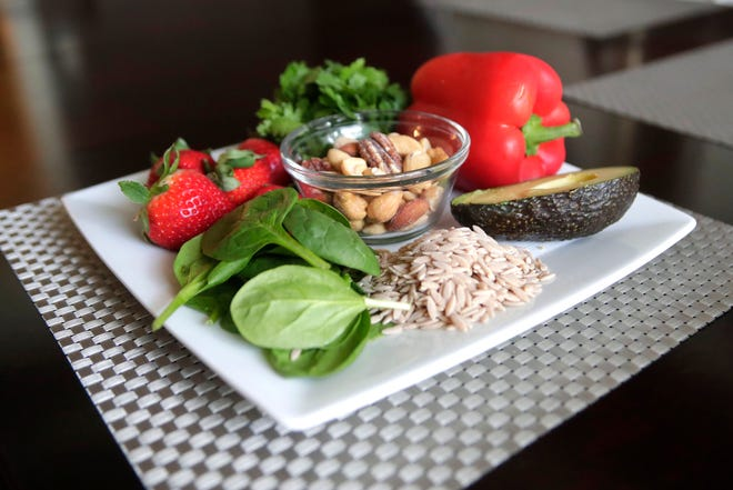 A plate of heart healthy foods prepared by Anna Jones, a local dietician and nutritionist, Friday Feb. 15, 2019. The plate includes strawberries, cilantro, a red bell pepper, half an avocado, whole grains, spinach, and a bowl of mixed nuts.