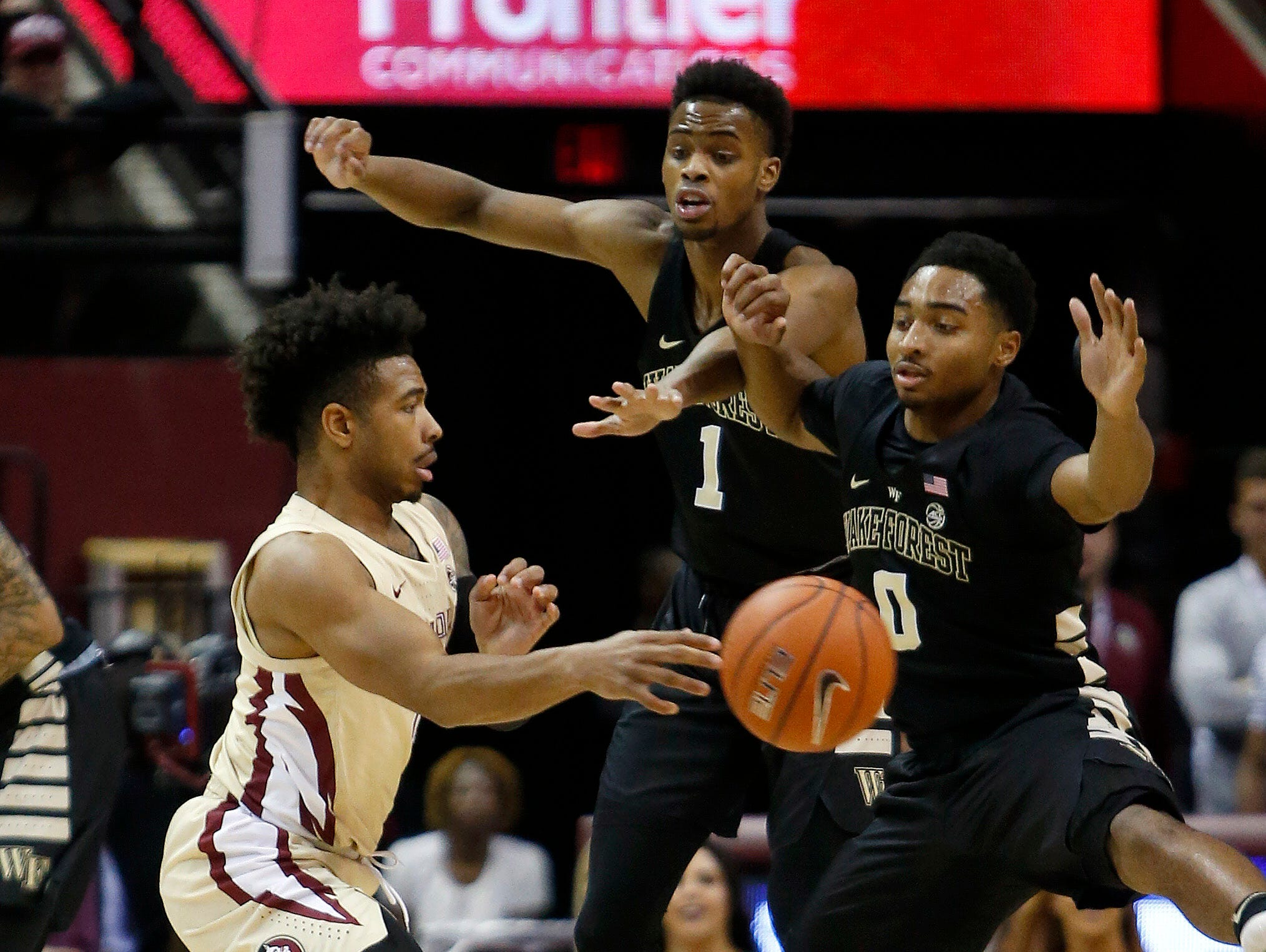 Feb 13, 2019; Tallahassee, FL, USA; Florida State Seminoles guard David Nichols (11) passes the ball around Wake Forest Demon Deacons guard Brandon Childress (0) and Demon Deacons forward Isaiah Mucius (1) during the first half at Donald L. Tucker Center. Mandatory Credit: Glenn Beil-USA TODAY Sports
