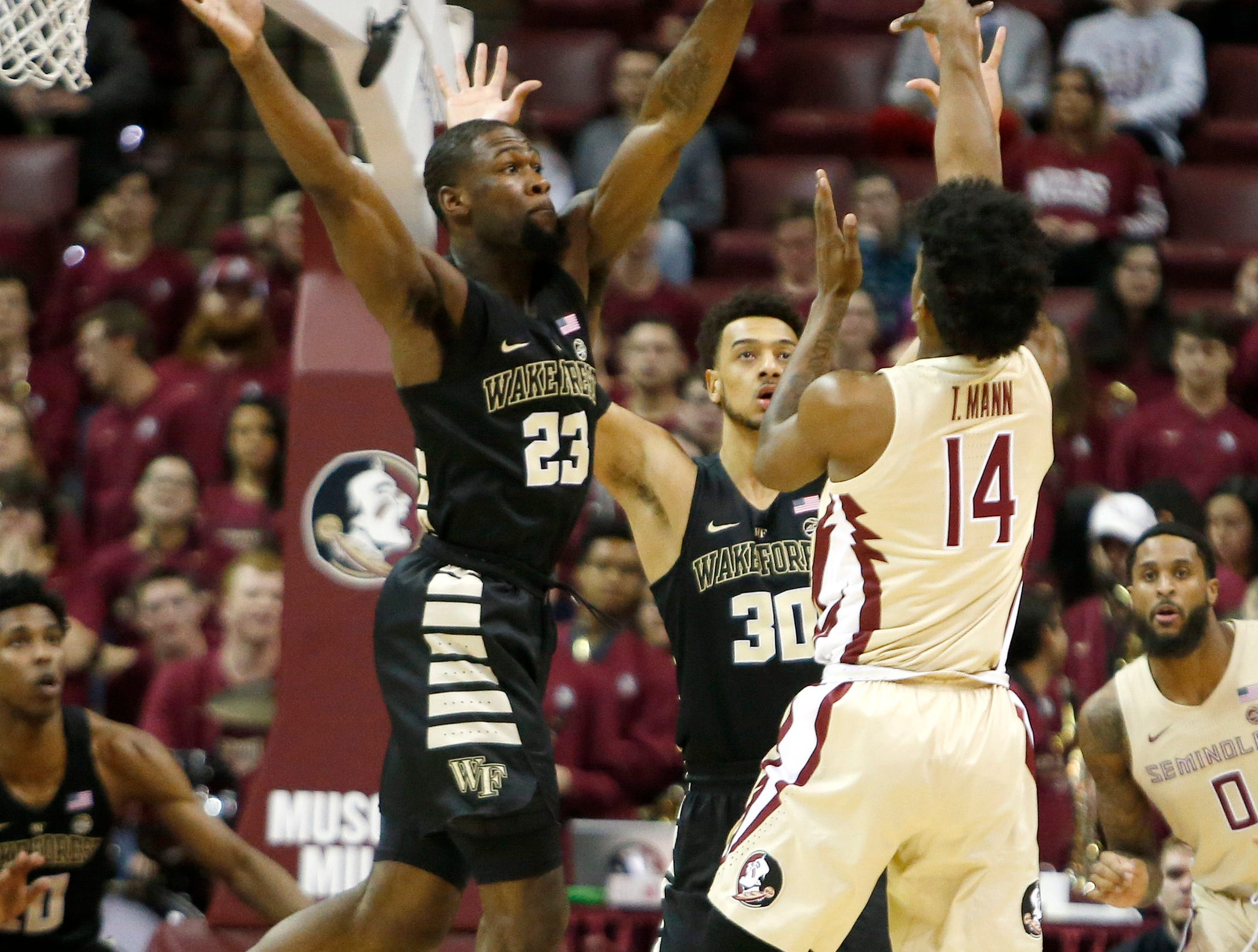 Feb 13, 2019; Tallahassee, FL, USA; Florida State Seminoles guard Terance Mann (14) passes the ball over Wake Forest Demon Deacons guard Chaundee Brown (23) and Demon Deacons center Olivier Sarr (30) during the first half of action at Donald L. Tucker Center. Mandatory Credit: Glenn Beil-USA TODAY Sports