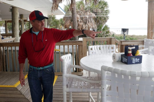 George Joanos, part owner of Blue Parrot Open Front Cafe on St. George Island, Fla., points to where the tiki bar is and talks about how it was unscathed by Hurricane Michael in Oct. 2018.