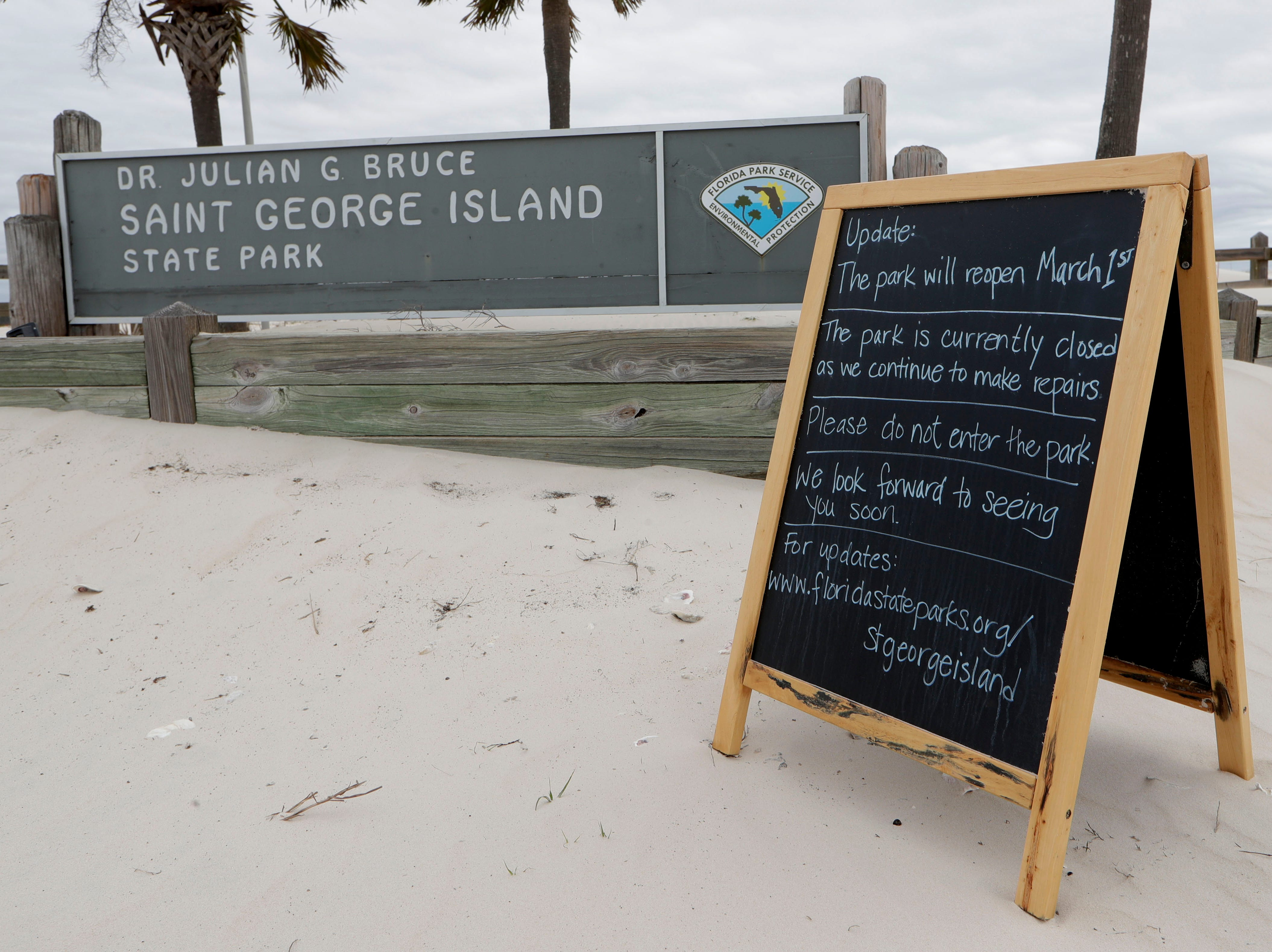 A chalkboard sign sits out front of the St. George Island State Park entrance telling guests about the park's plans to reopen on March 1, 2019.