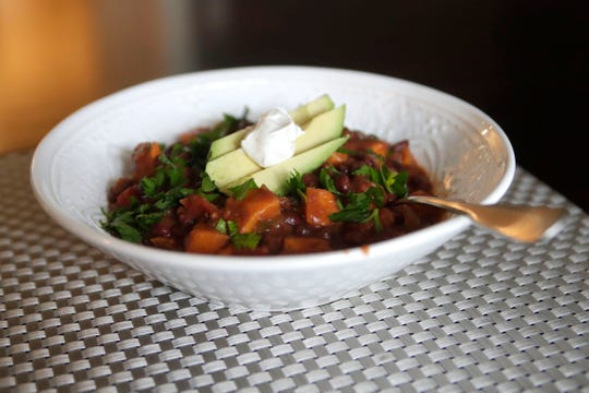 A bowl of sweet potato black bean chili topped with cilantro, avocado slices and a dollop of sour cream, a heart healthy recipe prepared by Anna Jones, a local dietician and nutritionist, Friday Feb. 15, 2019.