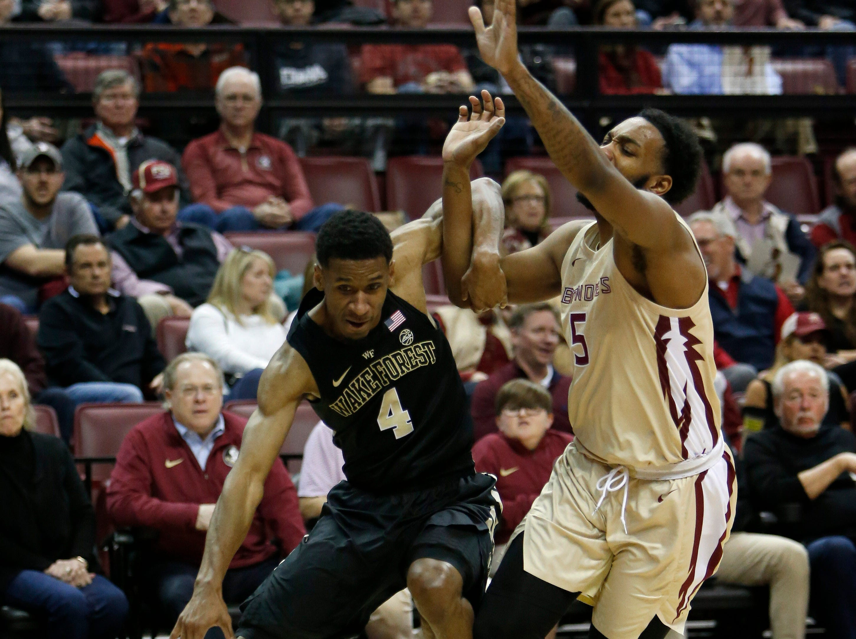 Feb 13, 2019; Tallahassee, FL, USA; Wake Forest Demon Deacons guard Torry Johnson (4) dribbles the ball around Florida State Seminoles guard PJ Savoy (5) during the first half of action at Donald L. Tucker Center. Mandatory Credit: Glenn Beil-USA TODAY Sports