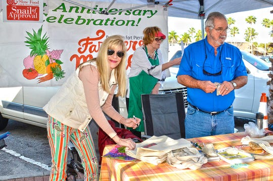 Artist Colleen Nash Becht, left, signs a 22nd anniversary Downtown Fort Pierce Farmers' Market bag, as Fort Pierce Mayor Linda Hudson and Tommy Patrick tend to other duties at the information desk Feb. 16.