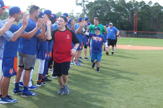 Special Olympics athletes run down a line getting high 5s from New York Mets players and coaches in Port St. Lucie on Sunday.