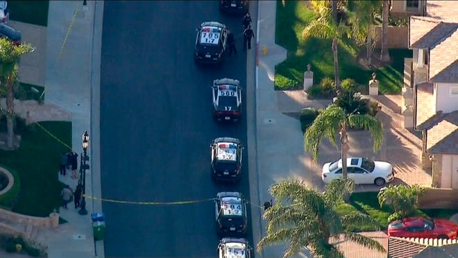 In this still image taken from KABC-TV, Los Angeles police officers secure a residence in Porter Ranch on Monday.