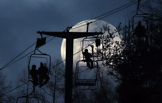 Skiers catch a quick look at the Super Snow Moon before clouds moved in, as it rose in the eastern sky over Thunder Ridge Ski Area in Patterson, Feb. 18, 2019.
