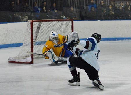 Mahopac goalie Logan MacDougall slides to block a shot by Rye Town/Harrison's Eric Mehlman during the third period on Monday, Feb. 18, 2019 at Playland.