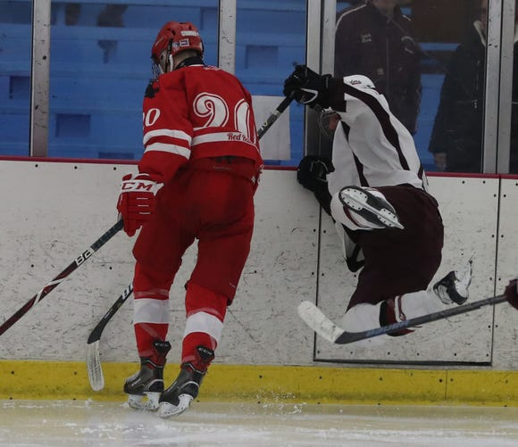 Jack Brosgol of Scarsdale flies into the boards after a hit by Luke Morris of North Rockland during a hockey playoff game at the Ice Hutch in Mount Vernon Feb. 18, 2019. North Rockland defeated Scarsdale 4-2.