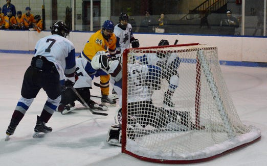 Mahopac forward Brian O'Shea flips in a second-period goal despite being surrounded during Monday's Division I quarterfinal against Rye Town/Harrison.