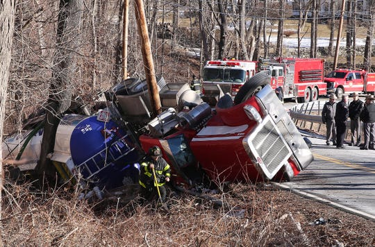 Croton Falls firefighters work at the scene of an overturned tanker truck that was carrying gasoline and diesel fuel on Route 116 in North Salem Feb. 19,  2019.