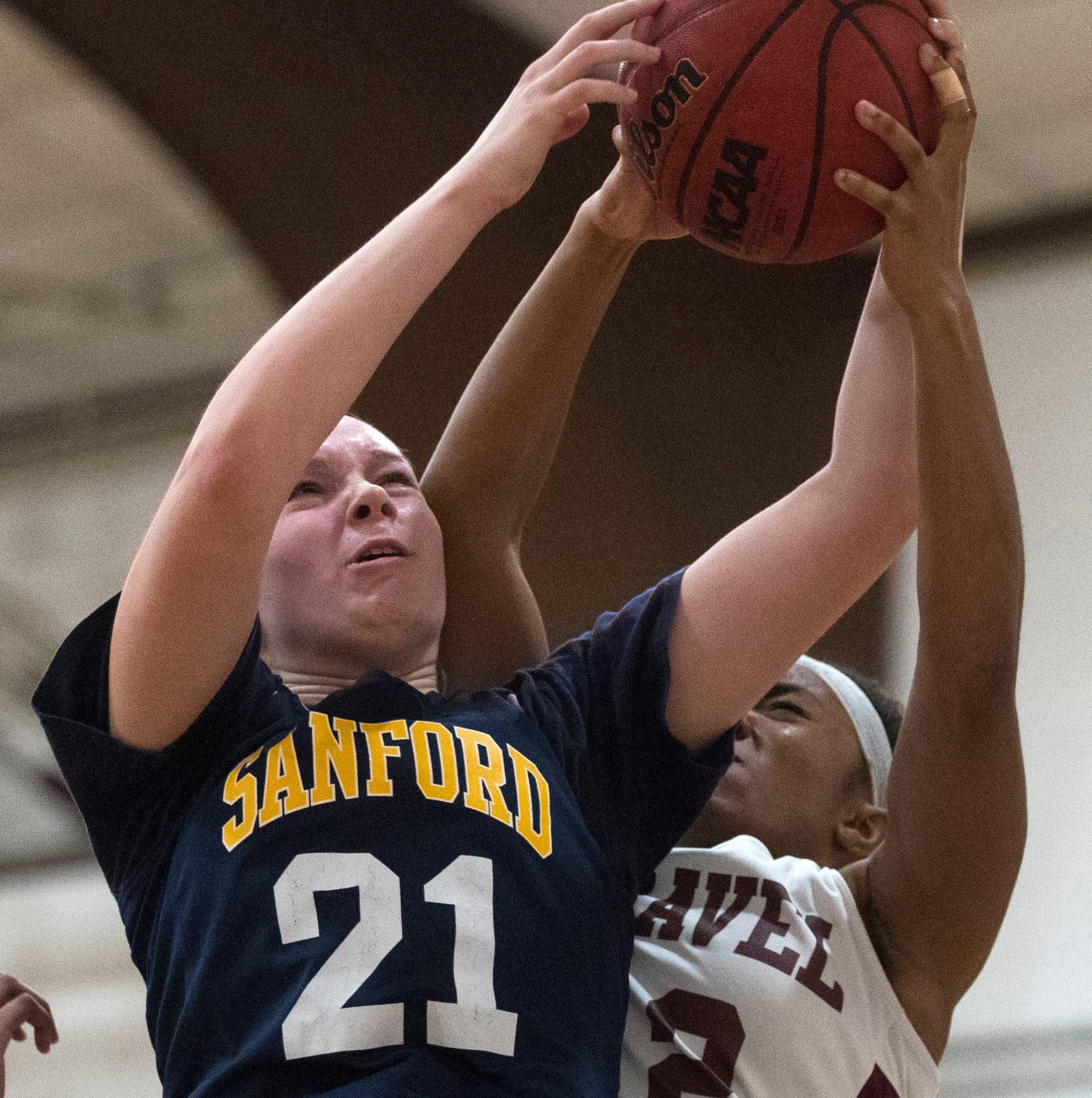 Sanford's Allie Kubek (21) grabs a rebound Monday...