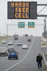Minnesota would become one of 18 states plus the District of Columbia that require drivers to use hands-free devices while phoning. This sign is in Delaware, which passed a hands-free cell phone law in 2010.