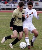 Rider's Ethan Havins fights with Aledo's Micco Little for possession Monday, Feb. 18, 2019, at Garnett Stadium. The Raiders defeated the Bearcats 2-1.