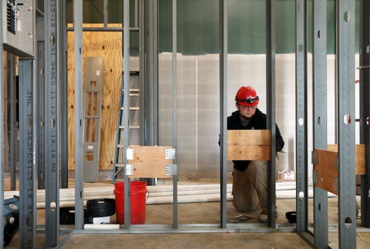 Steven Mitchell of Ables Heating, Cooling, Electrical and Refrigeration works in the Family Video building on Maple Avenue. The building is being divided, and part of it will house Hometown Urgent Care, which is expected to open April 7.