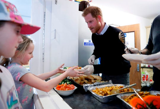 Prince Harry helps serve hot lunches during his visit to a Fit and Fed program in London on Feb. 19, 2019. The project offers activity sessions and a nutritious meal every day for local children.