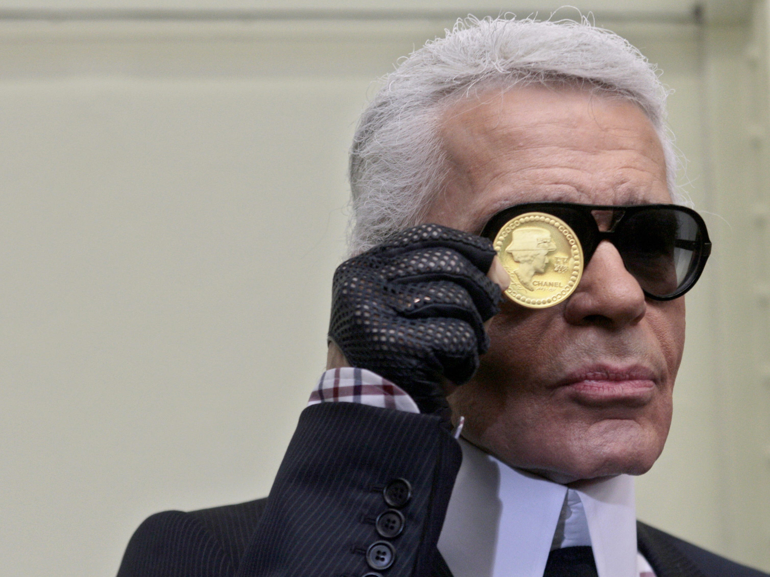 """Karl Lagerfeld presents a gold coin worth 5,900 euros (7,440 US dollars), representing French legend designer Gabrielle """"Coco"""" Chanel (1883-1971) on Nov. 19, 2008 at Paris Hotel des Monnaies. French Culture Minister Christine Albanel and Karl Lagerfeld were invited by the CEO of """"Monnaie de Paris"""" (The French Mint) Christophe Beaux to present the 10,000 copies first mint collection series specially designed by Lagerfeld."""